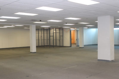 An empty flex space with an equipment cage in background